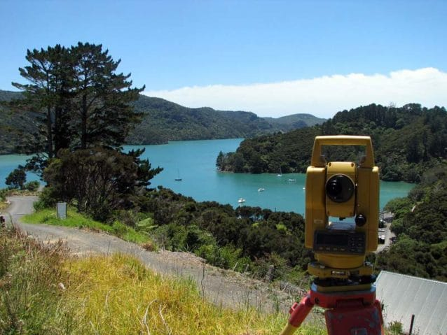 a total station in the foreground, overlooking a bay in Northland, New Zealand
